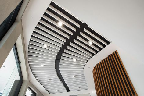 Asona Triton Baffle Beam™ 40 mm in white Sonatex™ was used to follow the curved wall.