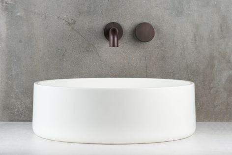 The sleek, minimalist design of the Zero wall basin mixer set is infused with the warm tones of Faucet Strommen's architectural finish in 'Antique Brass Light.'