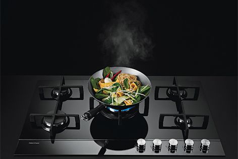 The Gas on Glass cooktop features polished stainless steel trim with sleek black glass.