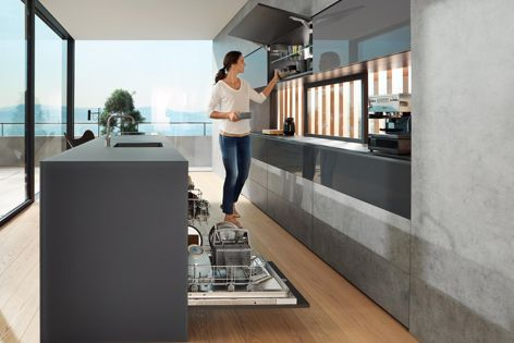 Cabinet doors that open over the kitchen bench can hinder movement. Installing an overhead lift system like Blum's AVENTOS HK top in these spaces can make a difference in everyday tasks like unpacking a dishwasher.