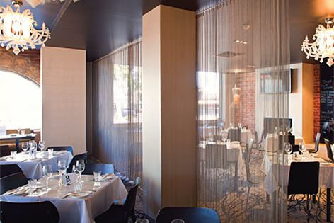 Transit mesh curtains have been used in this Adelaide restaurant to subtly partition rooms.
