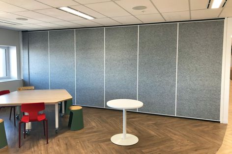 Bildspec manufactures acoustic dampening solid operable walls as well as double-glazed operable walls.