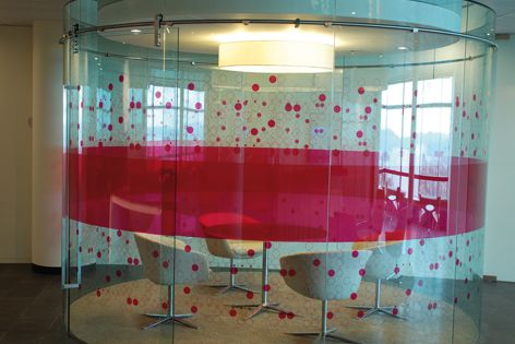 This dramatic circular freestanding meeting room features toughened curved glass panels.