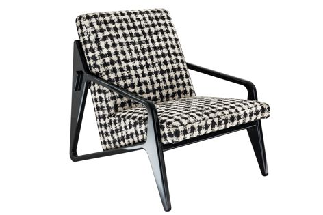 The Gio armchair has a geometric structure and can be upholstered in fabric or leather.