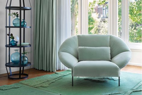 The cocoon-like Paipai armchair complemented by Ligne Roset's Babele shelf and Robin rug.